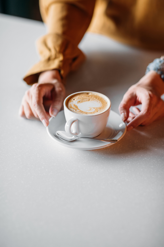 Close up of a woman holding a cup of coffee in a coffee shop. Only woman's hands are visible